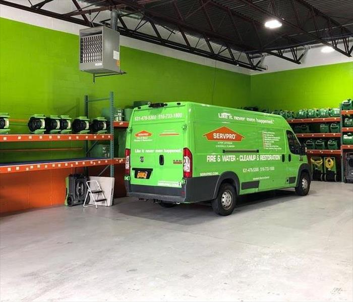 Warehouse with one a SERVPRO van and equipment stacked on shelves inside the warehouse.