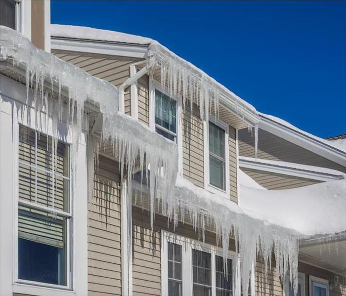 icicles hanging off the gutters and roof of beige house